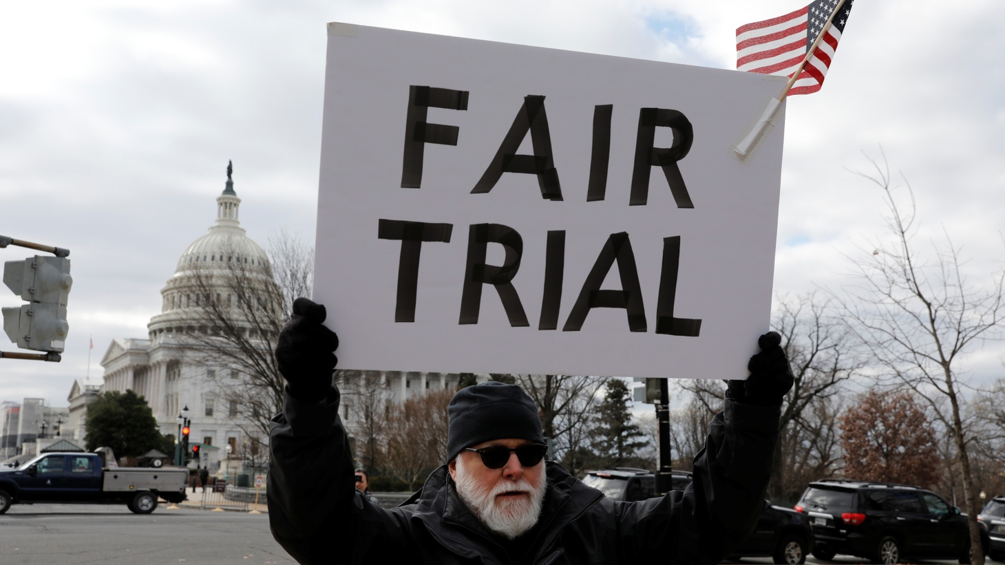 An activist holds a sign during a rally calling for witnesses in the Senate impeachment trial of U.S. President Donald Trump at the U.S. Capitol in Washington, U.S., January 29, 2020.