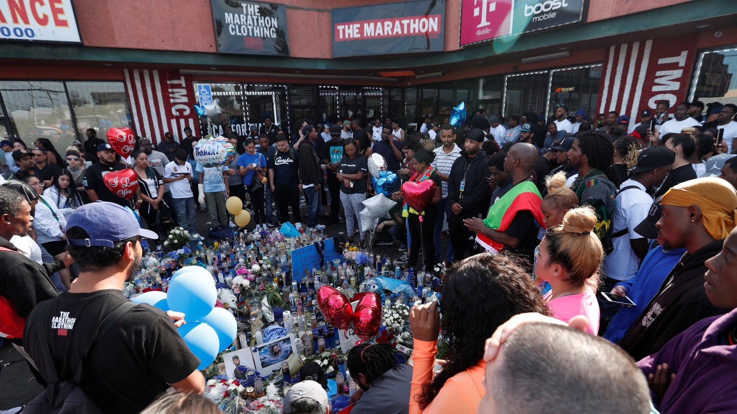 People gather around a makeshift memorial for Grammy-nominated rapper Nipsey Hussle who was shot and killed outside his clothing store in Los Angeles, California, U.S., April 1, 2019.