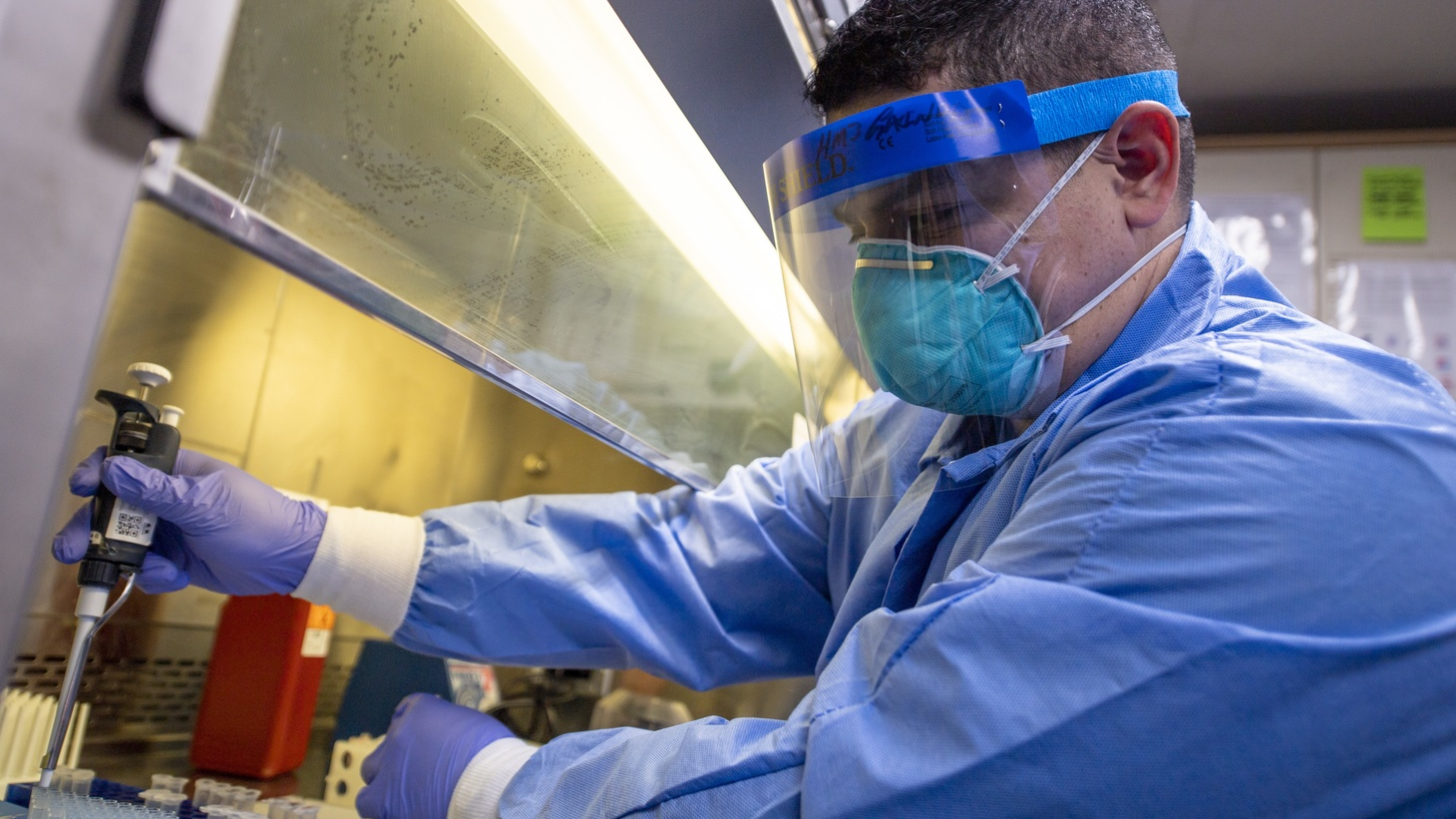 A sailor takes a test sample in the laboratory aboard USNS Mercy in Los Angeles, March 30, 2020. About four months into the COVID-19 pandemic, there still isn't enough testing available across the U.S.