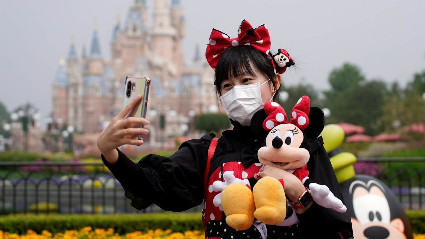 A visitor takes a selfie while wearing a protective face mask at Shanghai Disney Resort as the Shanghai Disneyland theme park reopens following a shutdown due to the COVID-19 outbreak.