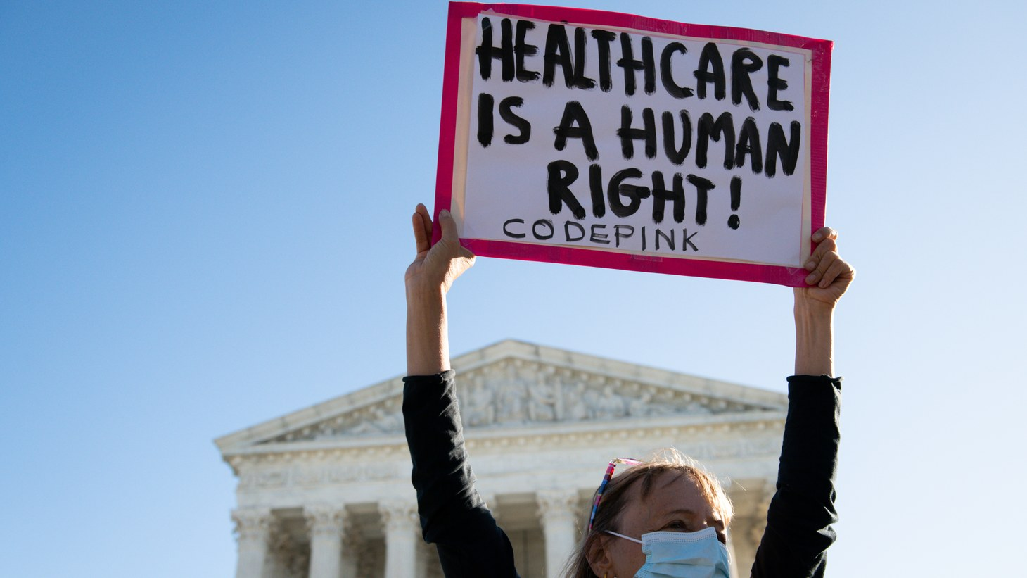 Madea Benjamin, with activist group Code Pink, holds a sign during a protest organized by SPACEs In Action at the U.S. Supreme Court, demanding the court preserve the Affordable Care Act in Washington, D.C., on November 10, 2020, amid the coronavirus pandemic.