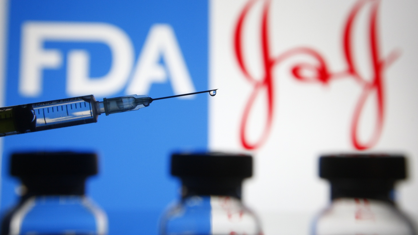 Food and Drug Administration (FDA) and Johnson & Johnson (J&J) logos are seen in front of a medical syringe and vials. On February 27, 2021, the FDA authorized Johnson & Johnson's coronavirus vaccine for emergency use.