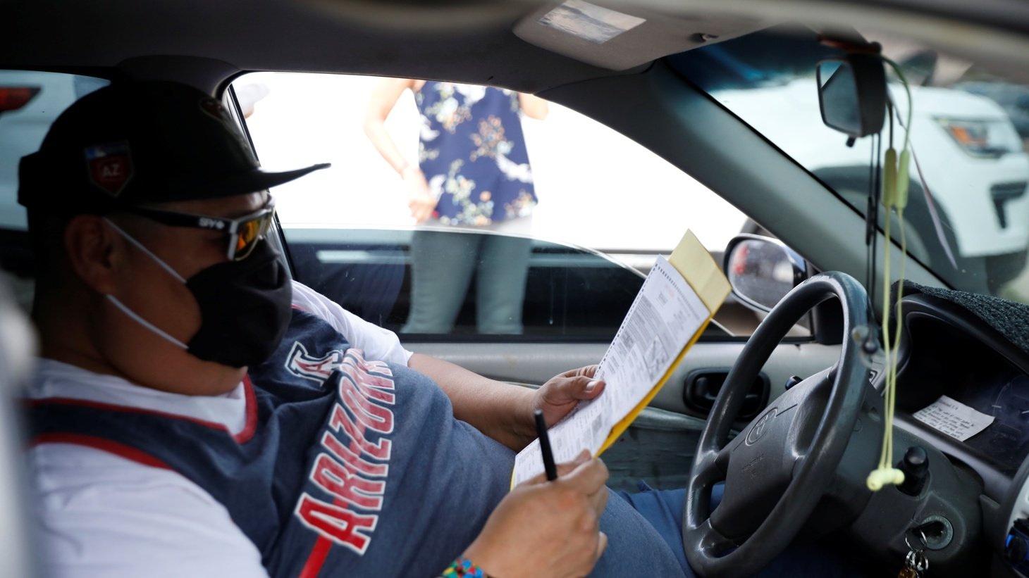 An Arizona resident casts his ballot from his car outside an election polling station in South Tucson, Arizona, U.S., November 3, 2020.
