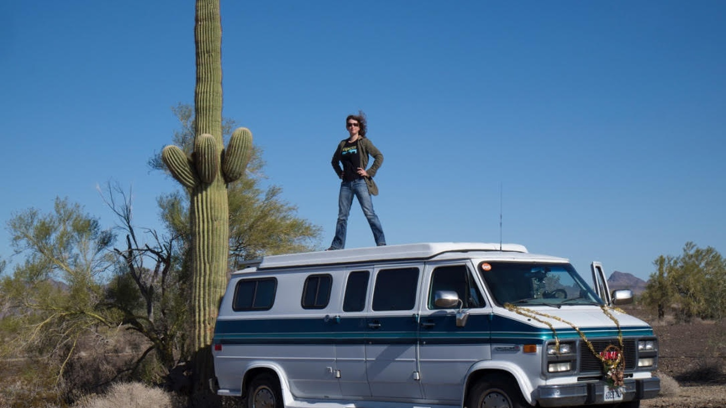 Jessica Bruder stands on top of her RV in the Sonoran Desert near Quartzsite, Arizona.