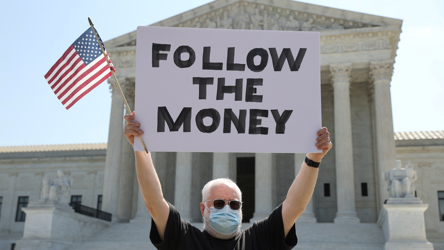 """Demonstrator Bill Christeson holds a sign reading """"follow the money"""" outside the U.S. Supreme Court, where justices ruled that a prosecutor in New York City can obtain President Donald Trump's financial records including tax returns, in Washington, U.S., July 9, 2020."""