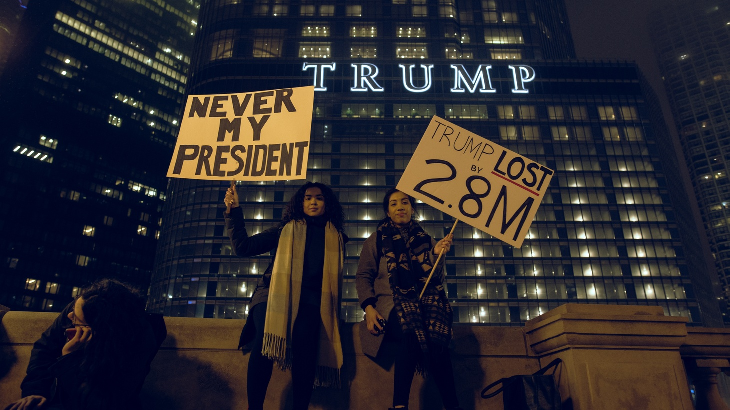 Two women hold signs at an anti-Trump protest near Trump Tower in Chicago.