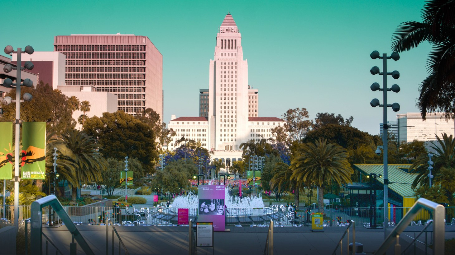 """A view of LA City Hall from Grand Park, as the park hosts the """"Celebration Spectrum"""" art exhibit, May 18, 2021. UCLA professor of architecture and urban design Dana Cuff says, """"Big parks, like Grand Park, show how active our downtown public spaces can be. So I think we have a good future for increasing public activity in our downtown areas."""""""