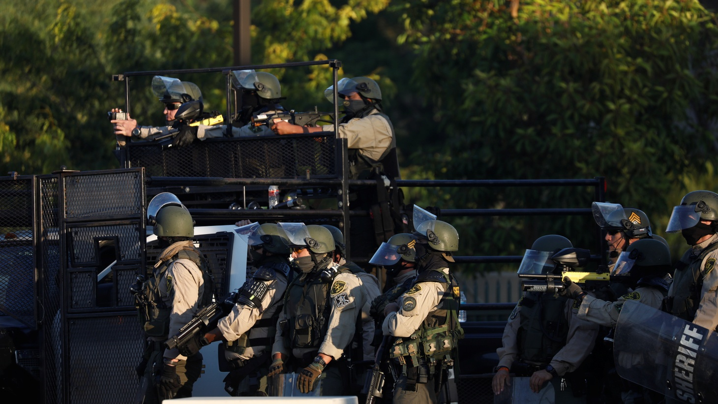 Law enforcement personnel wearing riot gear watch as demonstrators protest against the shooting of Dijon Kizzee by Los Angeles sheriff's deputies, outside the Los Angeles County Sheriff's department station in Los Angeles, California, U.S., September 1, 2020.