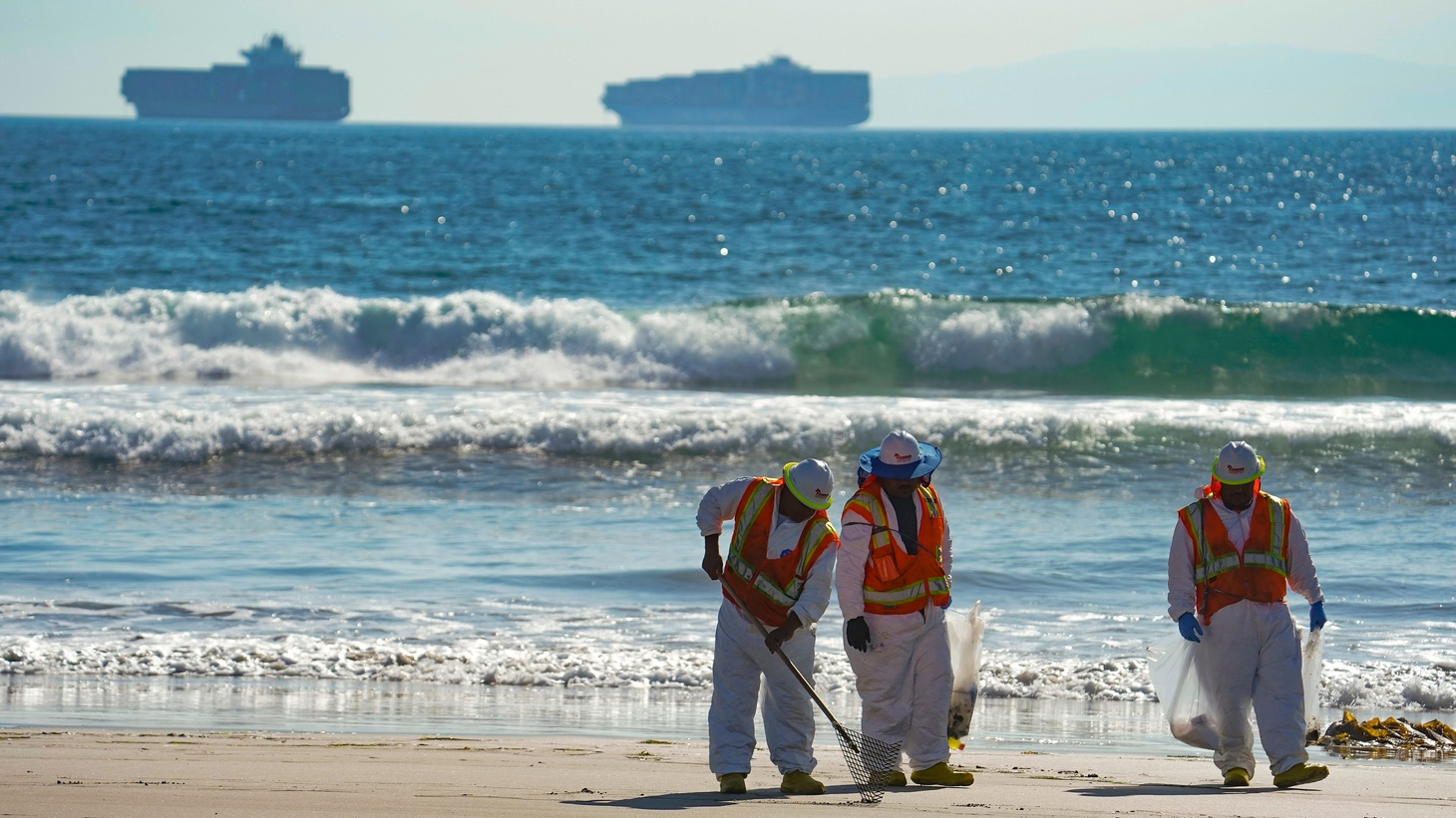 A cleanup crew walks along Huntington Beach, looking for spots of oil, October 5, 2021.