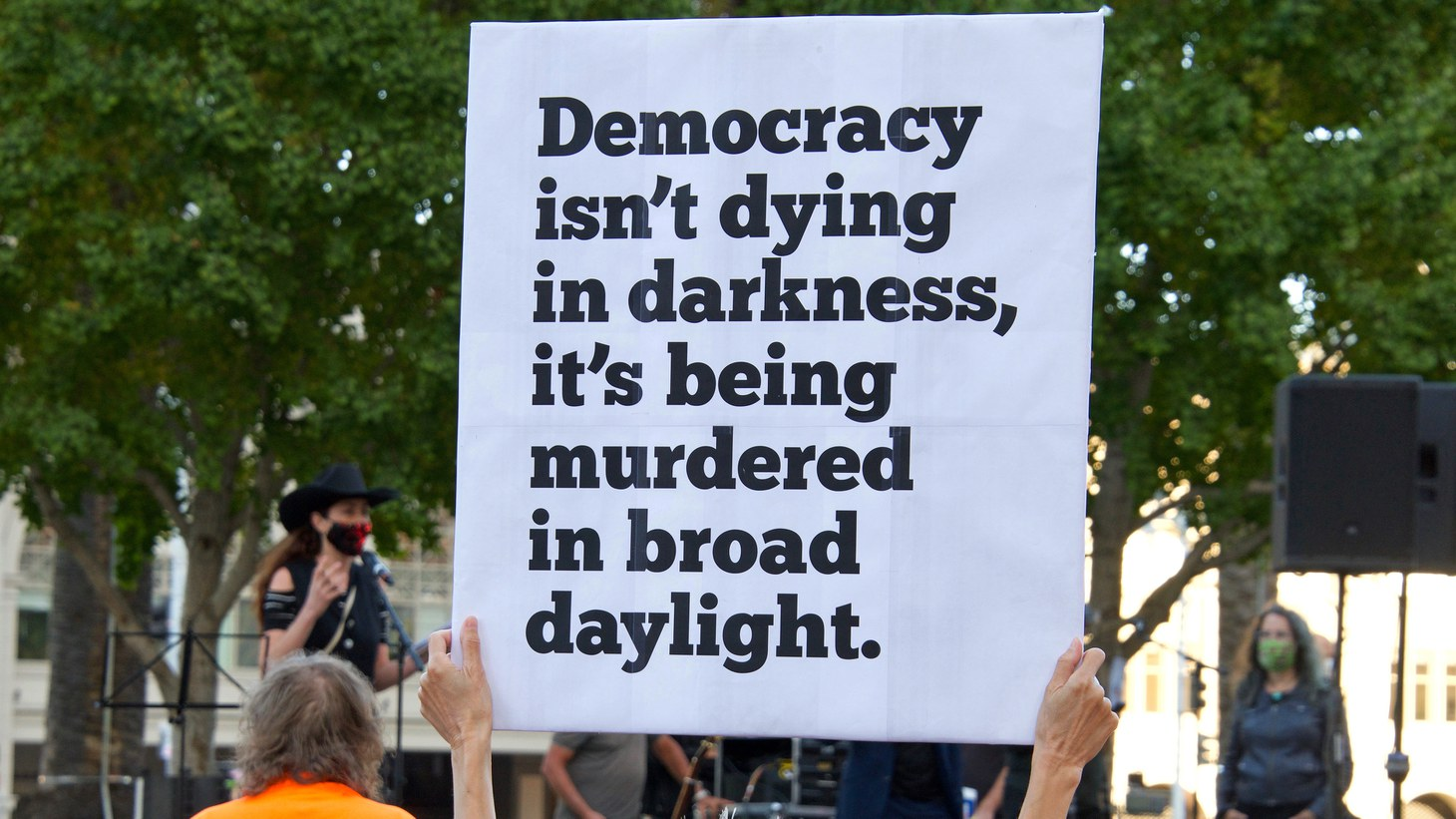 """During a """"Defend the Vote"""" rally, an activist holds a sign saying, """"Democracy isn't dying in darkness, it's being murdered in broad daylight,"""" in San Francisco, CA, Nov 4, 2020."""