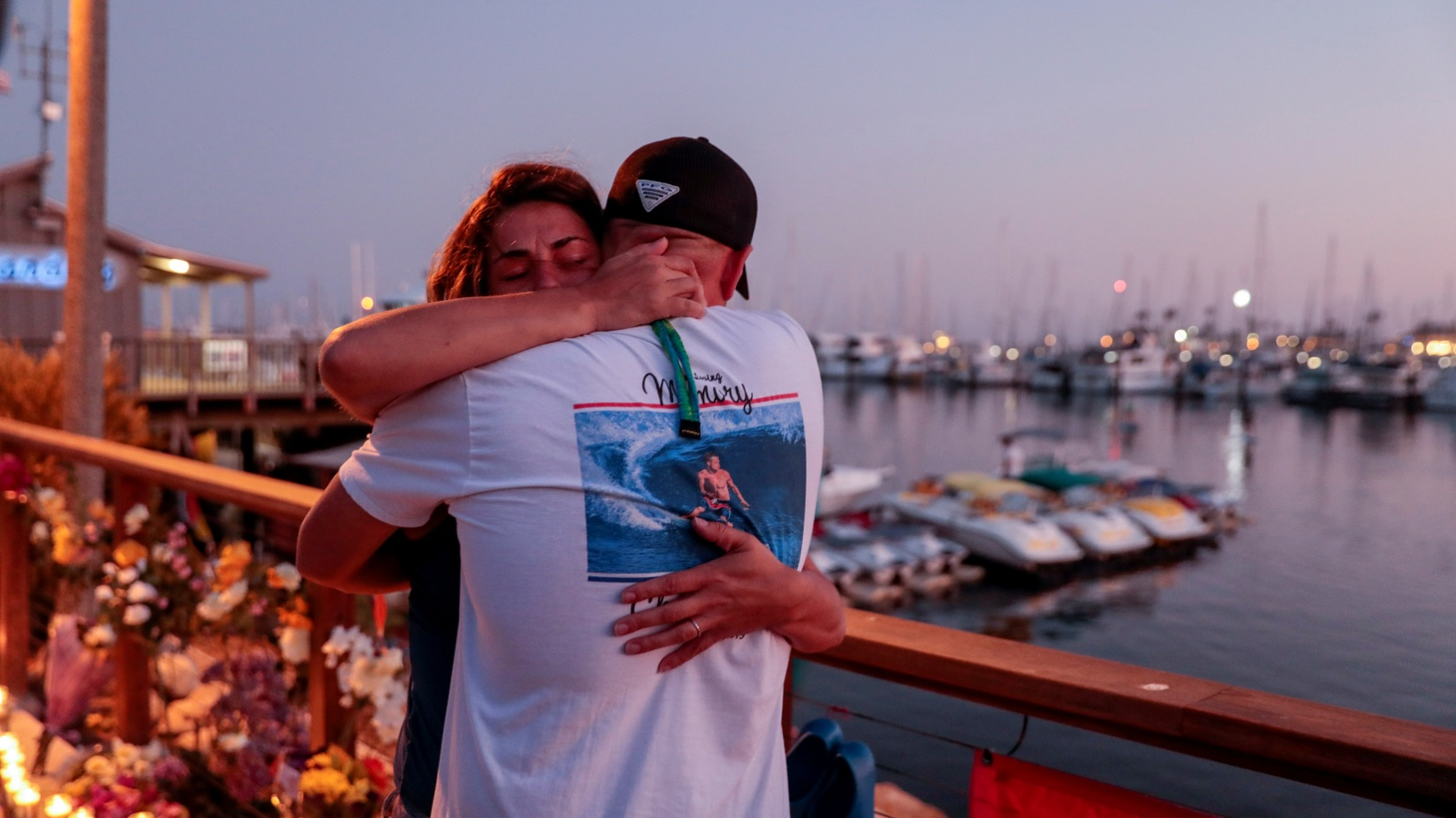 JJ Lambert and Jenna Marsala hug after hanging a scuba flag at a makeshift memorial near Truth Aquatics as the search continues for those missing in a pre-dawn fire that sank a commercial diving boat off a Southern California island near Santa Barbara, California, U.S., September 2, 2019.