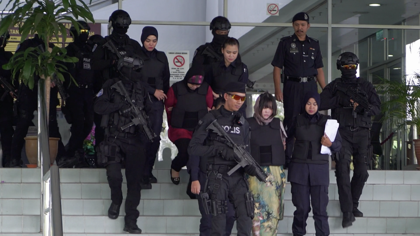 """Armed guards escort Doan Thi Huong and Siti Aisyah out of the courthouse in """"Assassins."""""""