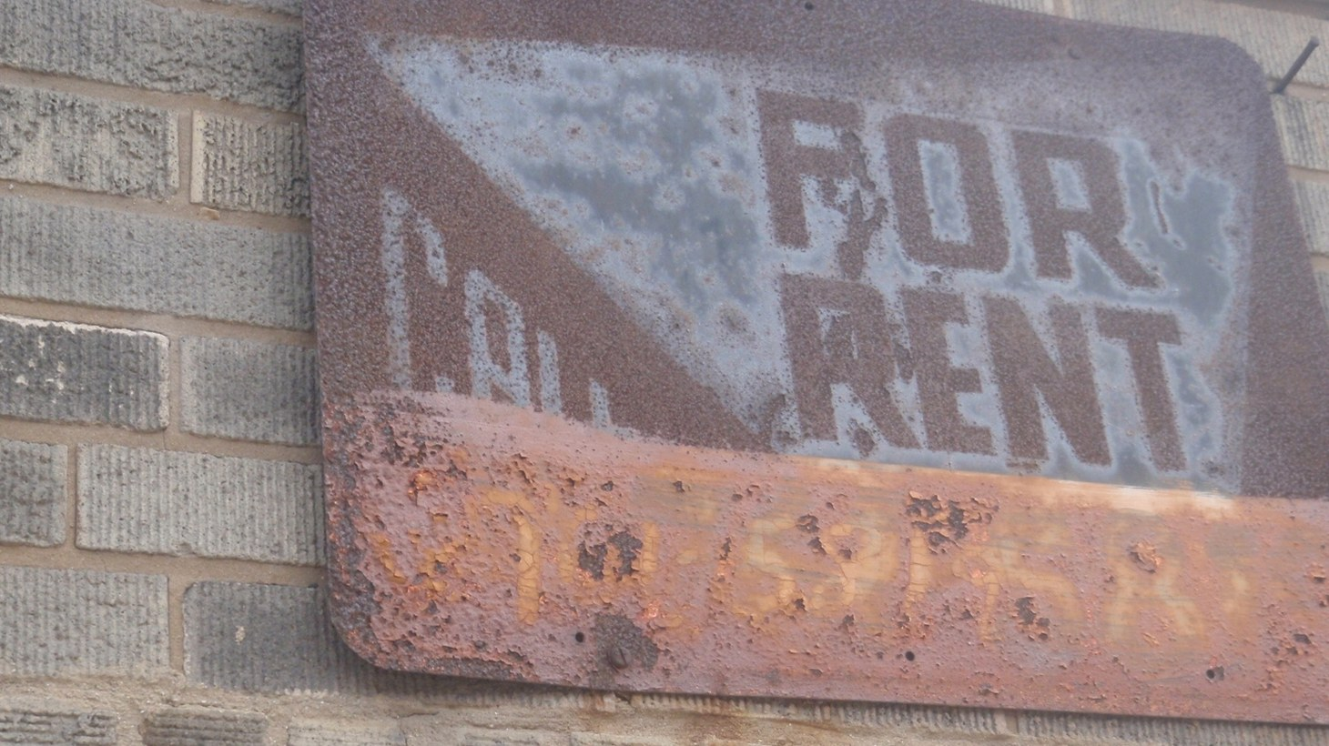 """Rusted """"for rent"""" sign."""
