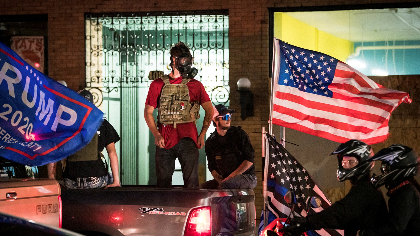 Supporters of U.S. President Donald Trump stand in flag-adorned pickup trucks during their caravan through Portland, Oregon, U.S. August 29, 2020.