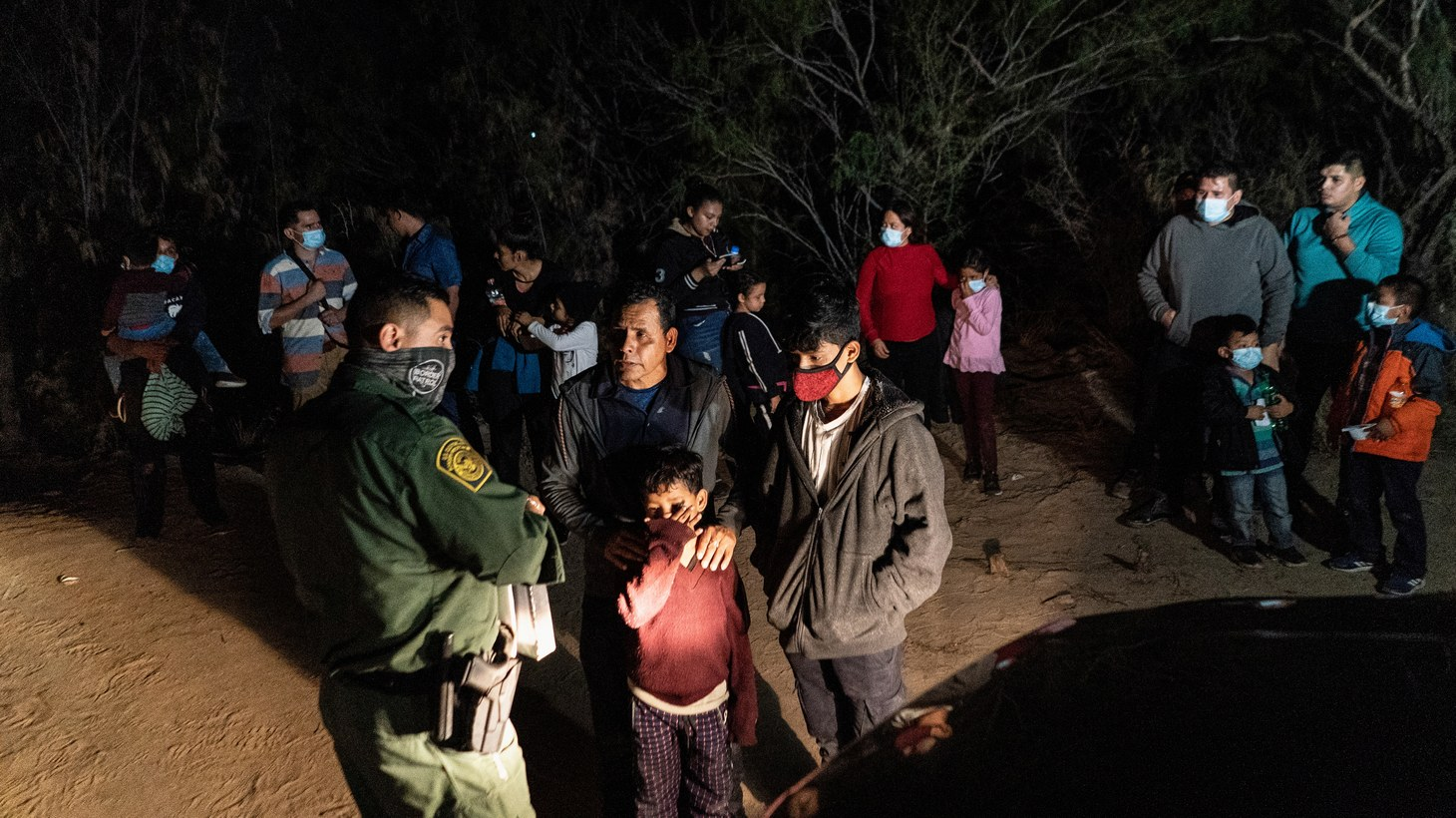 Asylum-seeking migrant families wait to be transported by the U.S. Border Patrol after crossing the Rio Grande river into the United States from Mexico in Roma, Texas, U.S., April 27, 2021.