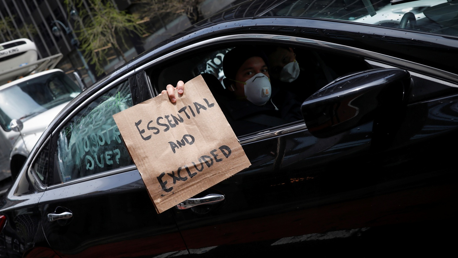 """A worker holds a sign from a car during a driving caravan demonstration in midtown Manhattan organized by """"Workers Justice Project,"""" protesting for rights of essential immigrant workers during the outbreak of COVID-19 in New York City, New York, U.S., April 21, 2020."""