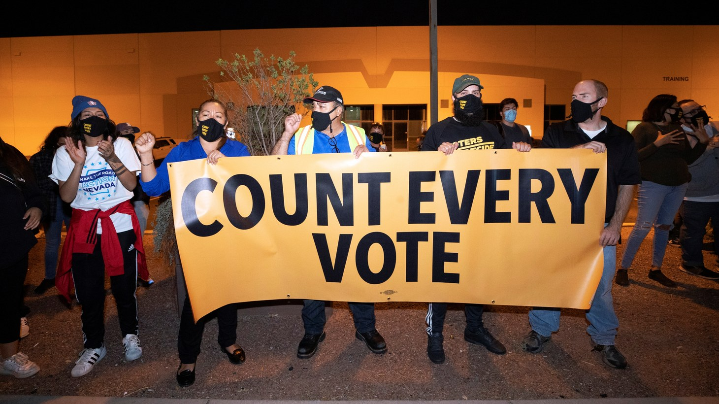 """Counter-protesters, organized by Make the Road Action Nevada and PLAN Action, hold a banner saying """"count every vote"""" during a """"Stop the Steal"""" protest by supporters of U.S. President Donald Trump at the Clark County Election Center in North Las Vegas, Nevada, U.S. November 4, 2020."""
