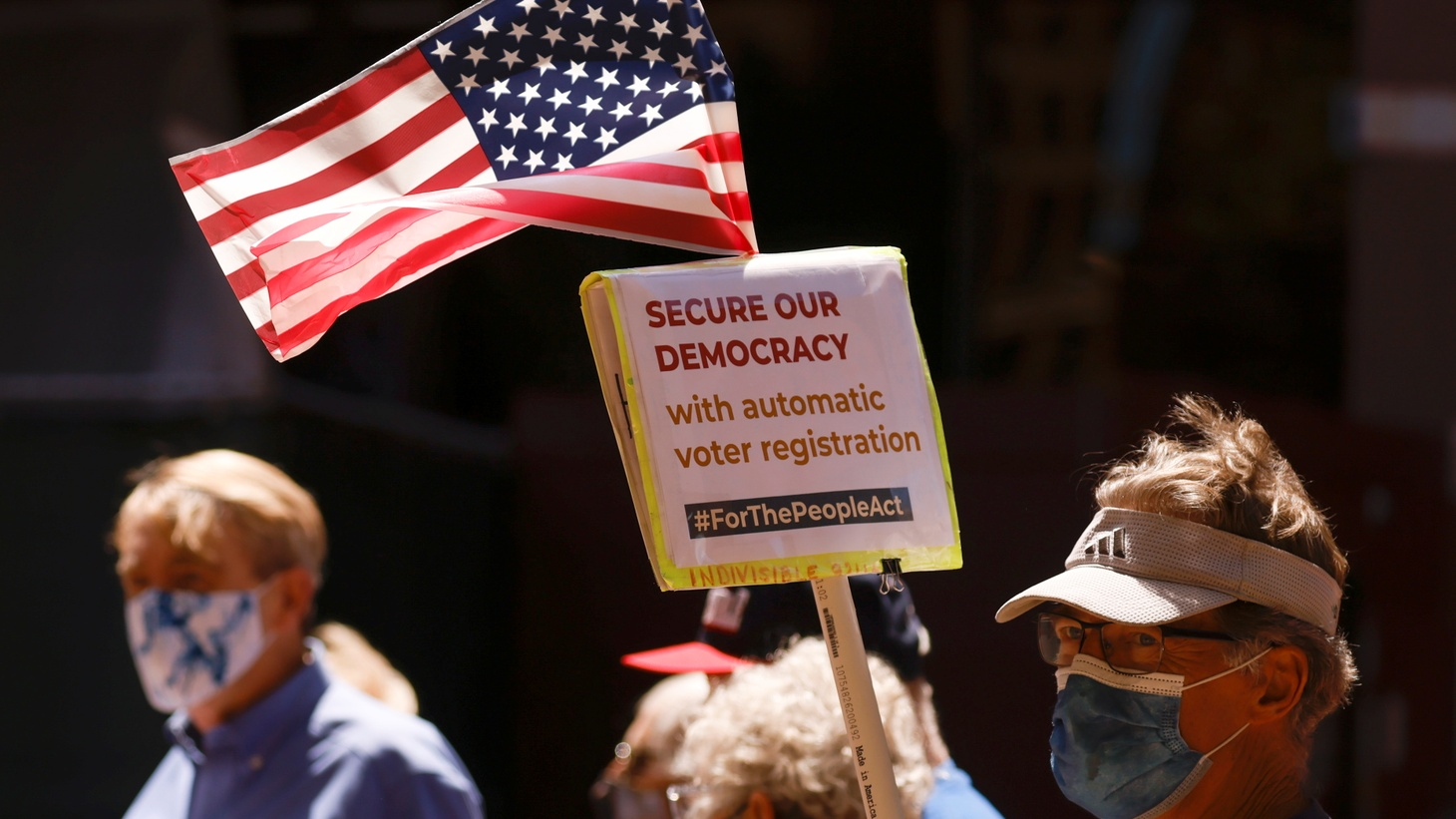 """Demonstrators demand the passage of the """"For the People Act,"""" intended to protect voting rights for all Americans, outside a federal building in San Diego, California, U.S., April 5, 2021."""