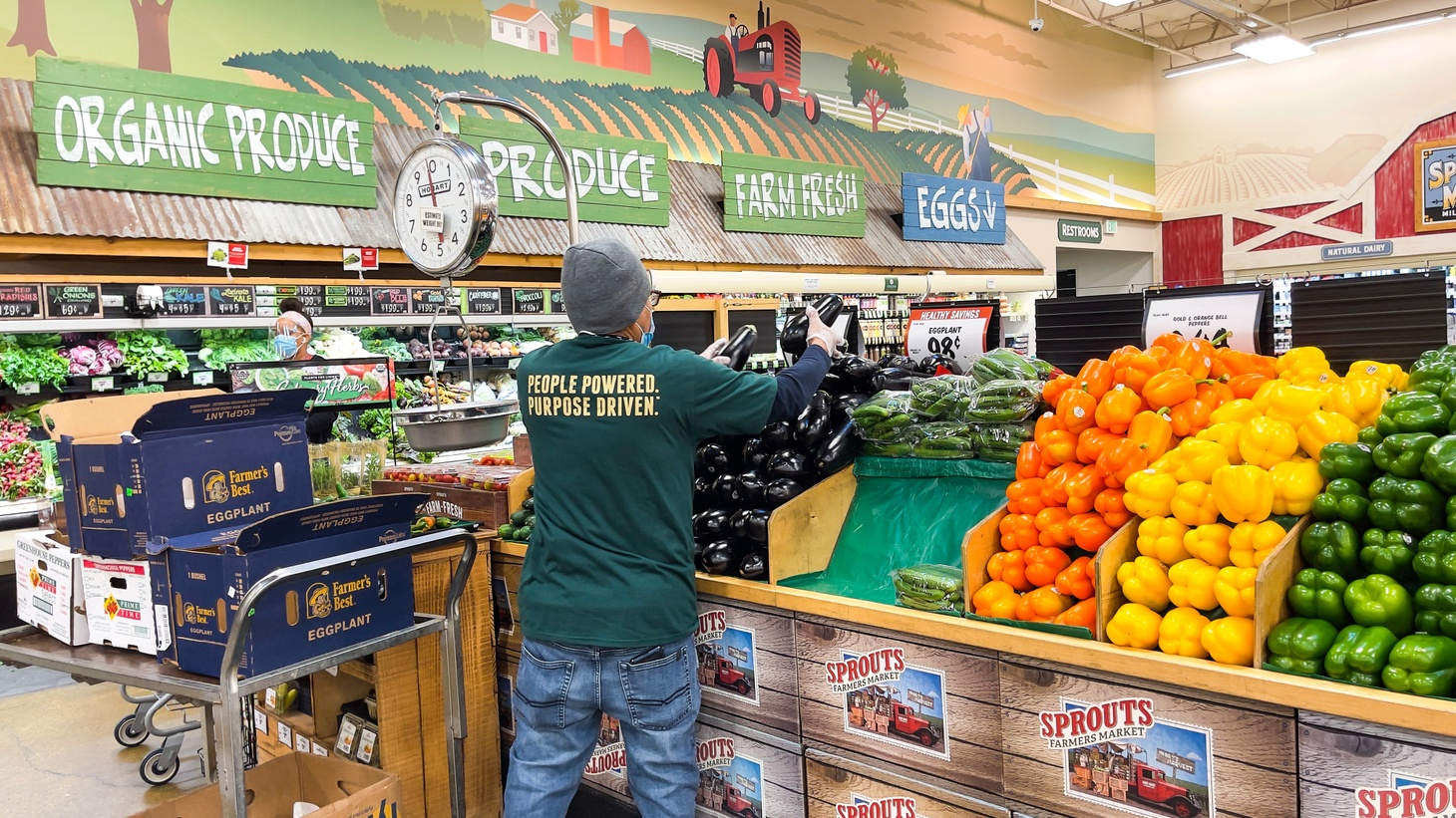 A masked worker stocks the produce section at Sprouts in Culver City, California, February 2021.