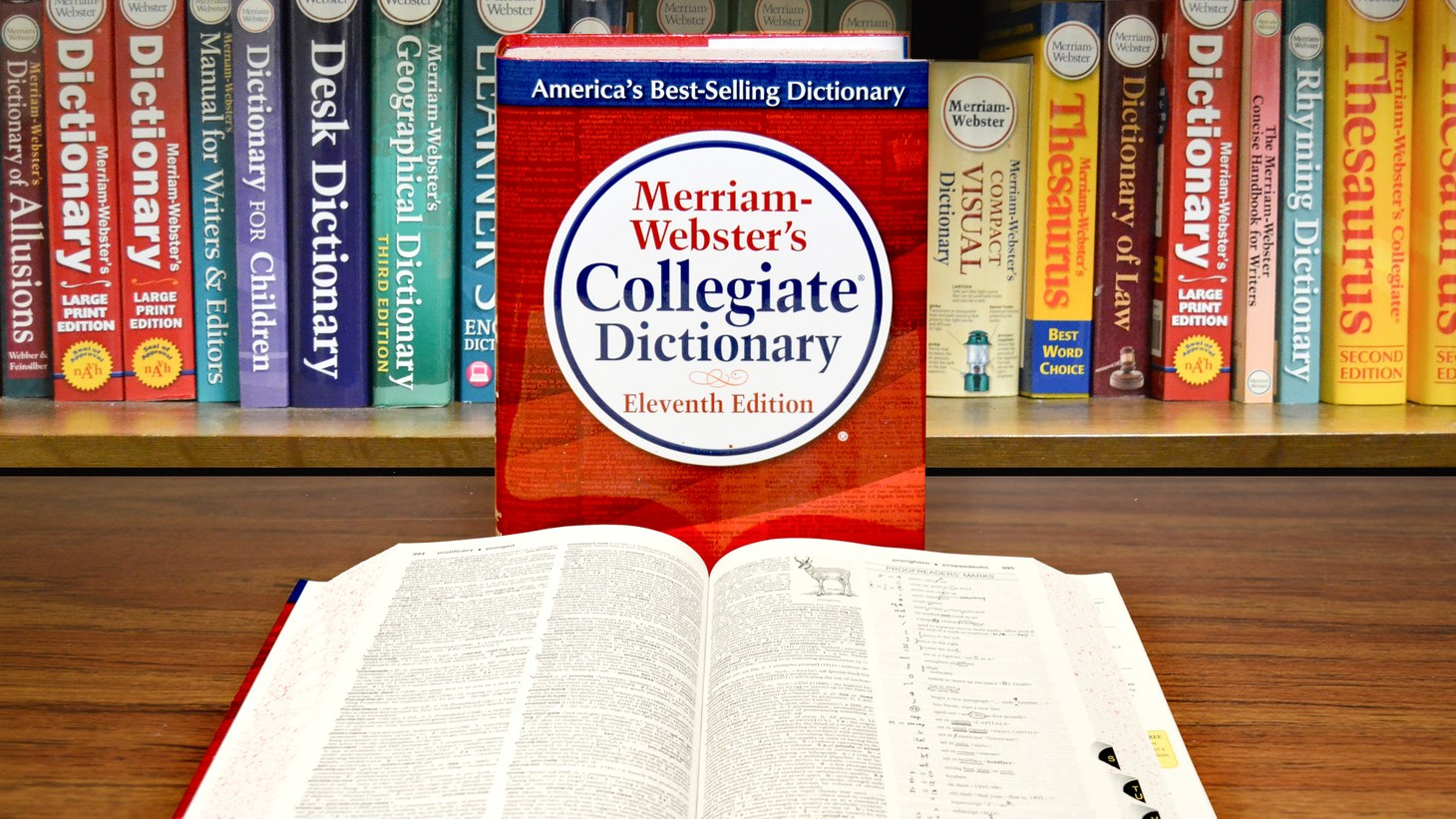 Merriam-Webster's Collegiate Dictionary, Eleventh Edition with open book and bookshelf.