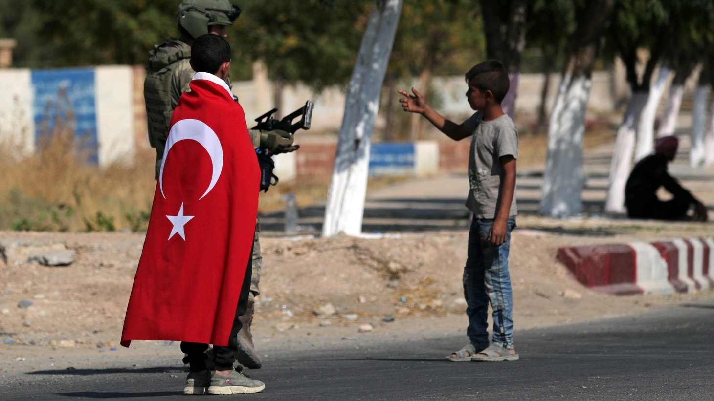 A boy wearing a Turkish flag stands next to a Turkish soldier as another boy gestures in the town of Tal Abyad, Syria October 23, 2019.