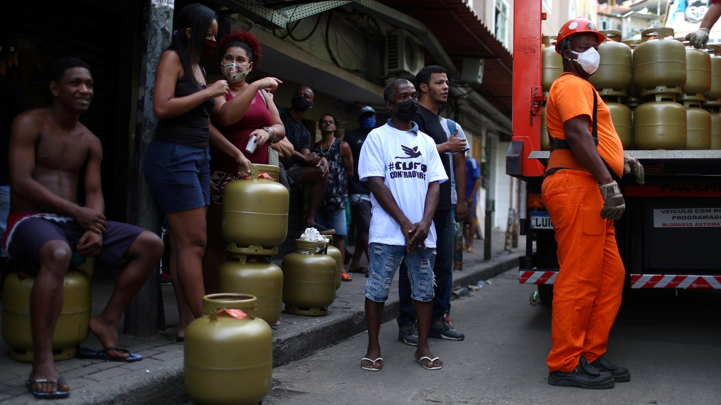 People wait to receive donations of cooking gas bottles distributed by Central Unica das Favelas (CUFA), a Brazilian non-governmental organization, following the coronavirus disease outbreak, in the Rocinha slum in Rio de Janeiro, Brazil May 22, 2020.