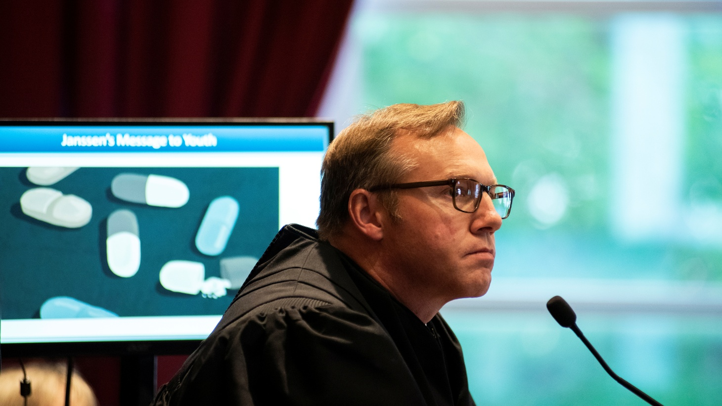 Judge Thad Balkman watches a video on the first day of a trial accusing Johnson & Johnson of engaging in deceptive marketing that contributed to the national opioid epidemic in Norman, Oklahoma, U.S. May 28, 2019.