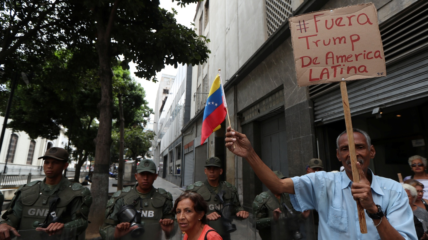 A supporter of Venezuela's President Nicolas Maduro holds a sign reading 'Trump out from Latin America' while security force members stand guard near the National Assembly building in Caracas, Venezuela May 21, 2019.