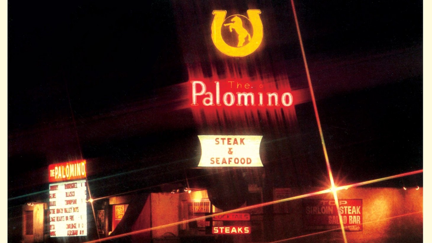 A postcard featuring an image of the exterior of the Palomino Club, formerly located at 6907 Lankershim Blvd, North Hollywood. From William Thomas, the then owner of the Palomino, the postcard has printed information on the back that promotes the Palomino as a filming location.