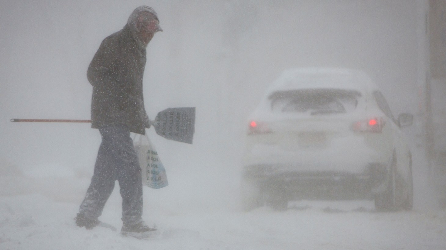 A man crosses a street in whiteout conditions during a winter storm in Buffalo, New York, U.S., January 30, 2019.
