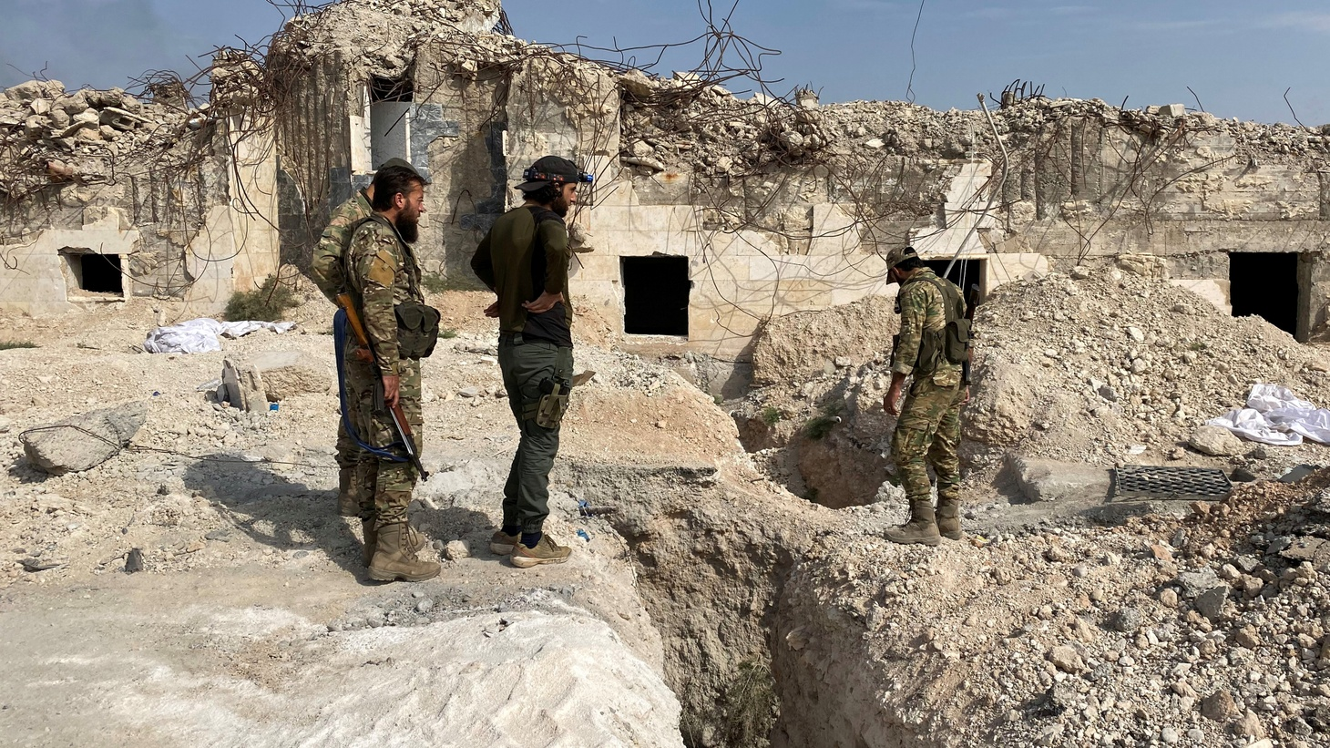 Turkey-backed Syrian rebel fighters stand near underground tunnels said to be made by the Syrian Democratic Forces (SDF) in Tal Abyad, Syria. October 17, 2019.