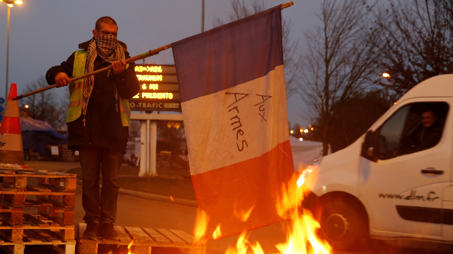 A protester wearing a yellow vest, the symbol of a French drivers' protest against higher diesel fuel prices, holds a flag near burning debris at the approach to the A2 Paris-Brussels Motorway, in Fontaine-Notre-Dame, France, December 4, 2018.