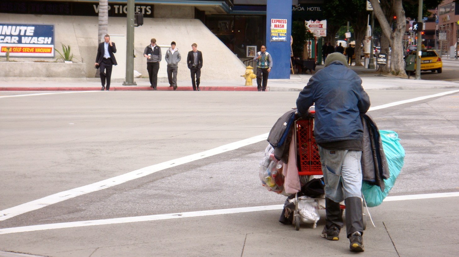 A homeless man crossing a busy intersection in DTLA.
