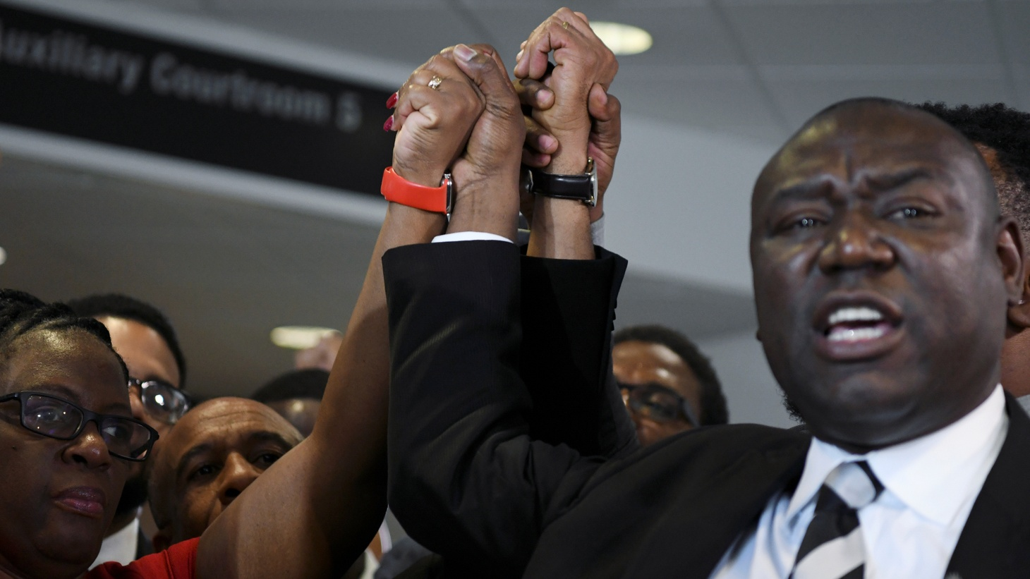 Botham Jean's mother Allison Jean and his father Bertram Jean raise their hand with their family attorneys, Daryl Washington, Benjamin Crump and Lee Merrit, after the conviction charge of murder was delivered for the trial of former Dallas police officer Amber Guyger, in Dallas, Texas, U.S. October 1, 2019.