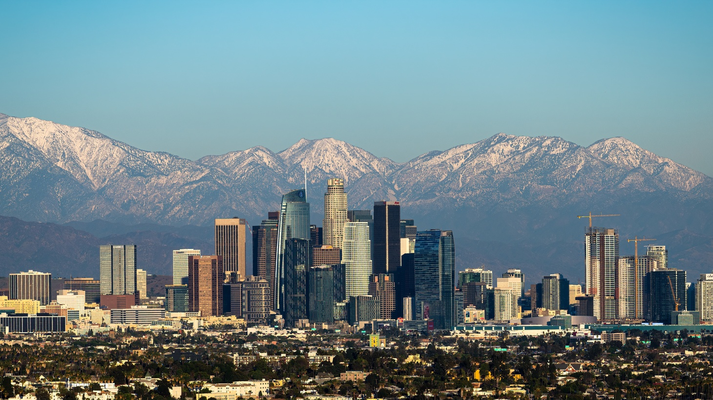 Snow-capped mountains are seen behind downtown LA, January 30, 2021.