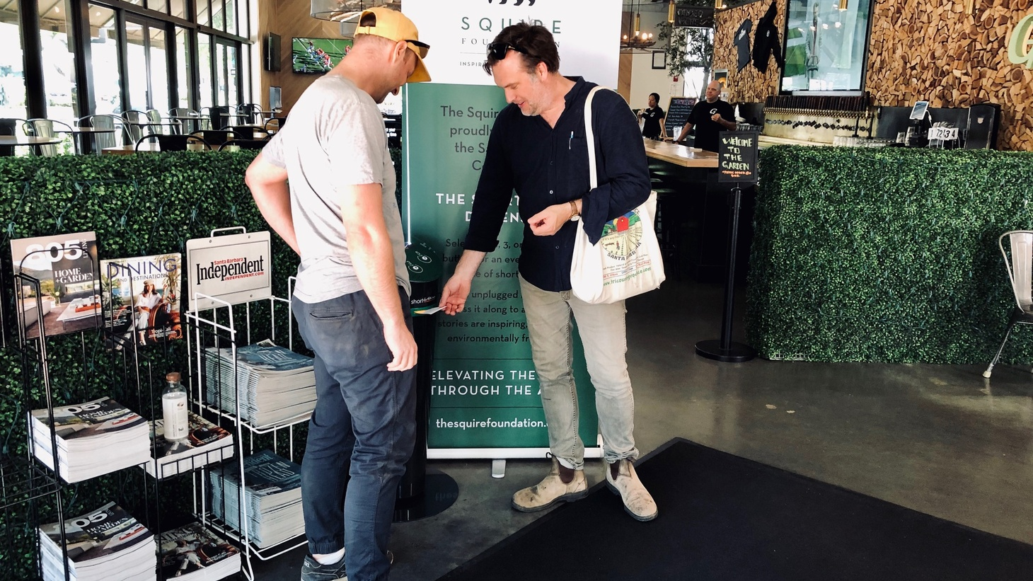 Dave Kilpatrick and Patrick Melroy wait for their on-the-go literature at the Short Edition Story Dispenser at the Santa Barbara Public Market.