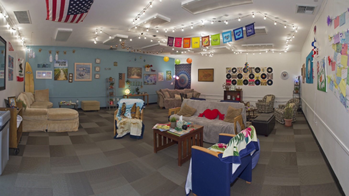 """View of the """"Reflection"""" room. Student interns designed the room to resemble an apartment in Isla Vista. The furniture and wall decorations reflect the Southern California lifestyle. Visitors were invited to relax and meet together in the room."""