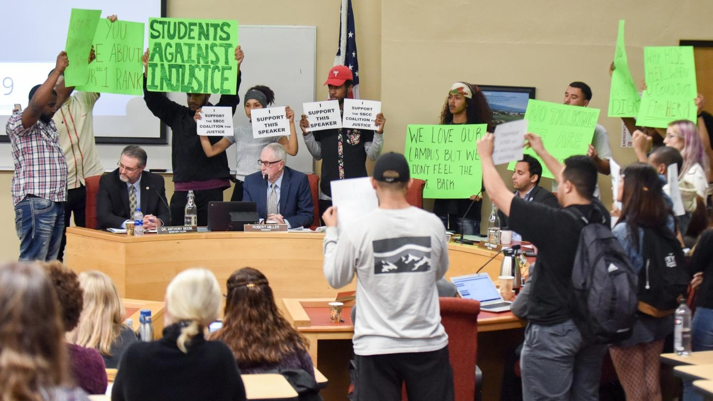 SBCC President Anthony Beebe (sitting on left) amidst a group of silent protesters at a Board of Trustees meeting in January.