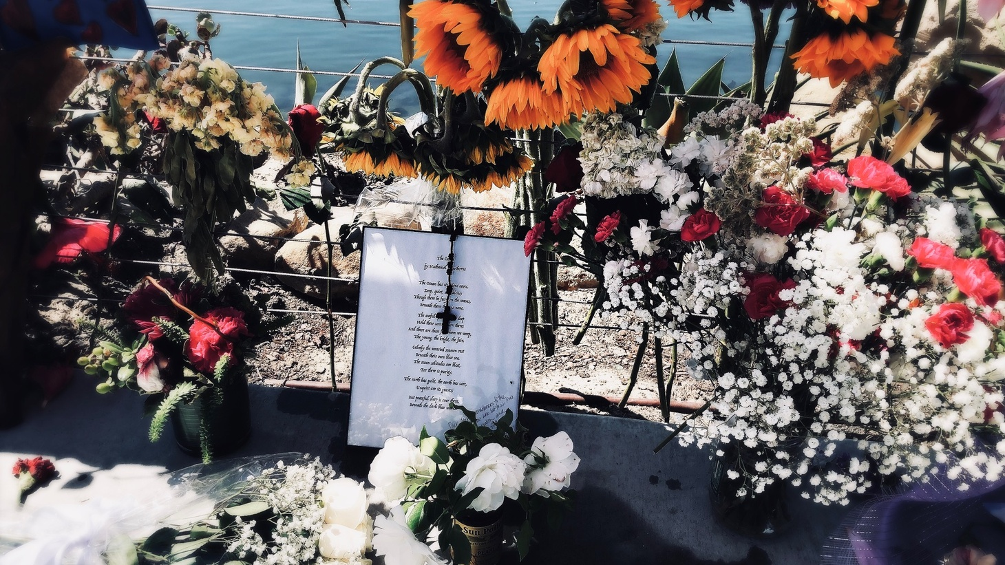 Mourners bring candles and flowers to the makeshift memorial at the Santa Barbara Harbor.