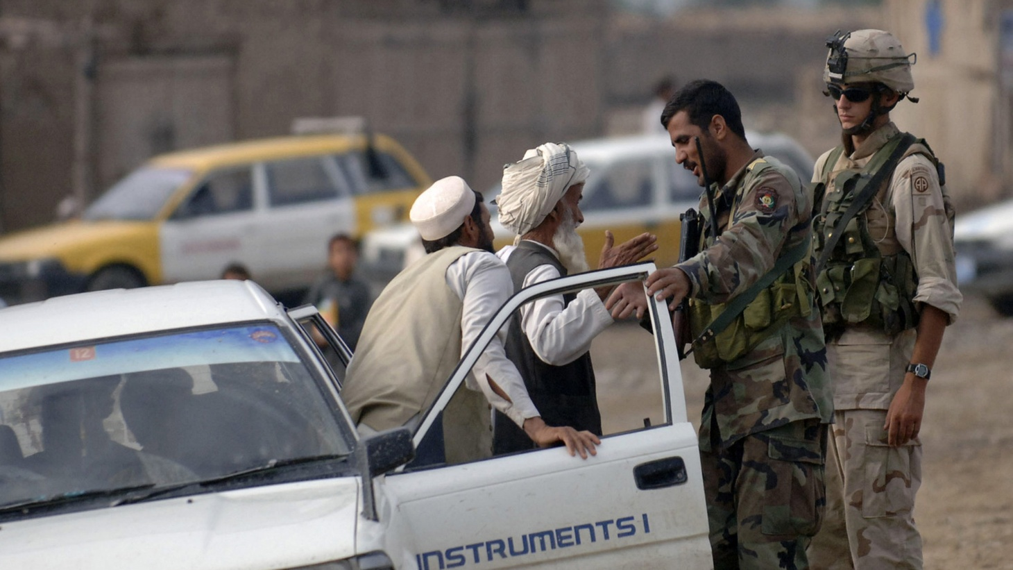 Personnel from the Afghanistan National Arm yand a US Army Soldier from A Company, 2/504 Parachute Infantry Regiment, 82nd Airborne Division, Alpha Company 2/504 Parachute Infantry Regiment, set up a temporary vehicle checkpoint in the city of Bak, in support of Operation Enduring Freedom.
