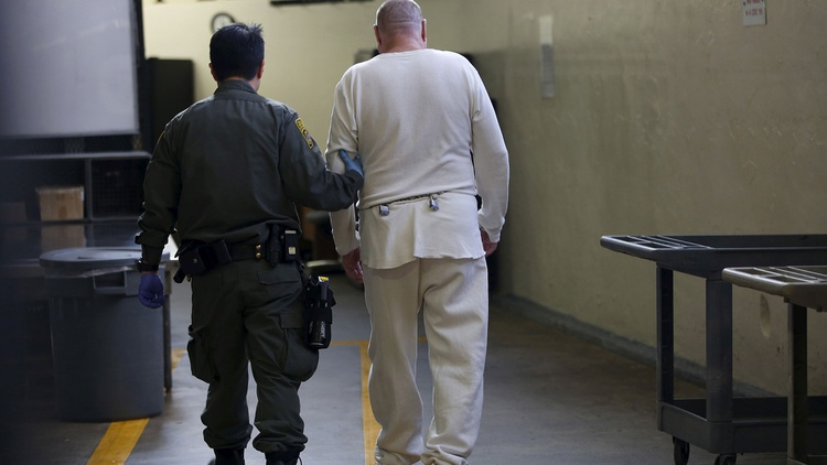 A guard escorts a condemned inmate down a corridor in the East Block  during a media tour of California's Death Row at San Quentin State Prison  in San Quentin, California December 29,…
