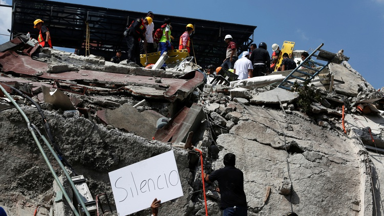 "A man holds up a sign that reads ""silence"" as rescue personnel look for people underneath the rubble of a collapsed building after an earthquake hit Mexico City, Mexico September 19,…"