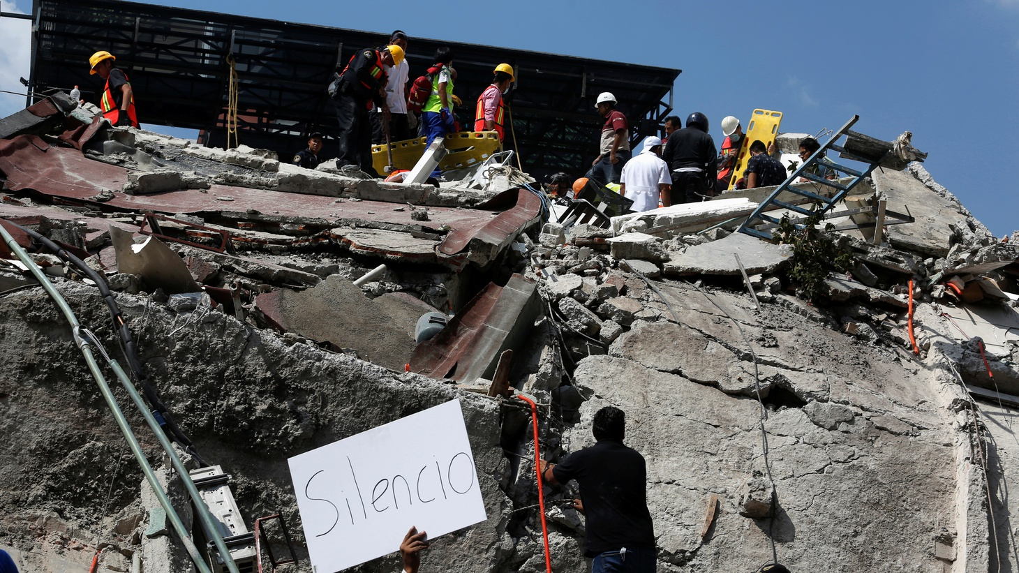 "A man holds up a sign that reads ""silence"" as rescue personnel look for people underneath the rubble of a collapsed building after an earthquake hit Mexico City, Mexico September 19, 2017."