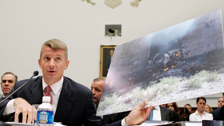 Blackwater CEO Erik Prince holds a photograph of the remains of a blown up vehicle in Iraq while testifying before the House Oversight and Government Reform Committee  on Blackwell…