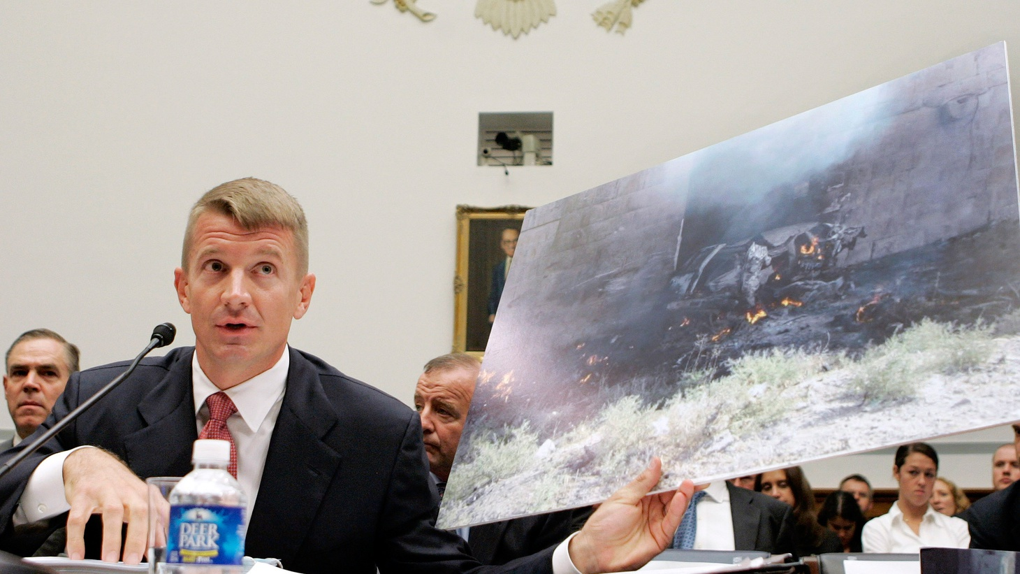 Blackwater CEO Erik Prince holds a photograph of the remains of a blown up vehicle in Iraq while testifying before the House Oversight and Government Reform Committee  on Blackwell security contracting in Iraq and Afghanistan, October 2, 2007.