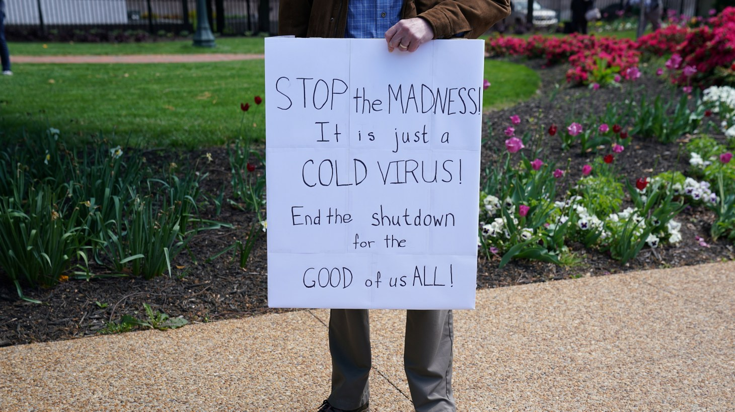 A lone demonstrator holds a sign in opposition to Virginia's stay-at-home order and business closures in the wake of the coronavirus disease (COVID-19) outbreak during a protest against the lockdown measures in Richmond, Virginia, U.S., April 16, 2020.
