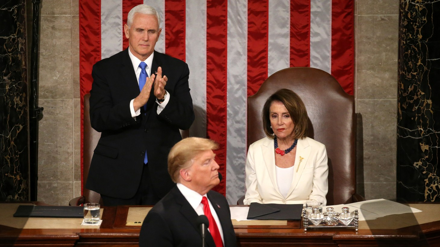 Speaker of the House Nancy Pelosi (D-CA) reacts alongside Vice President Mike Pence as he applauds U.S. President Donald Trump during his second State of the Union address to a joint session of the U.S. Congress in the House Chamber of the U.S. Capitol on Capitol Hill in Washington, U.S. February 5, 2019.