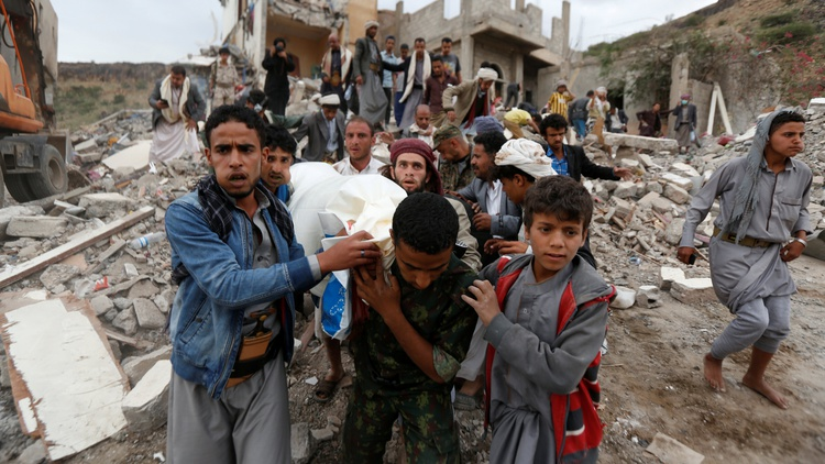 People carry the body of Muhammad Mansour recovered from under the rubble of a house destroyed by a Saudi-led air strike in Sanaa, Yemen.